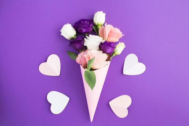 Fleurs blanches, roses et violettes dans un cône papier rose et coeurs roses sur le tableau violet gros plan