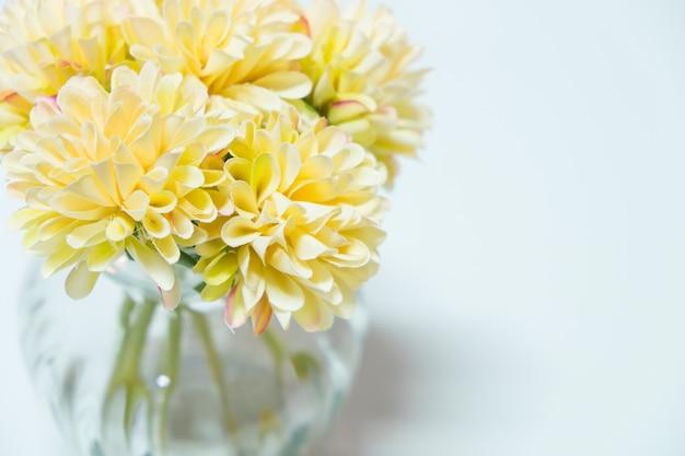 Les fleurs blanches sont disposées dans un vase, placé sur une table blanche.