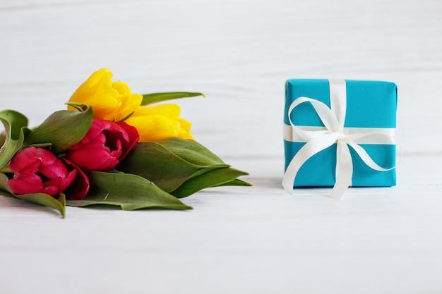 Des fleurs et une boîte avec un cadeau.