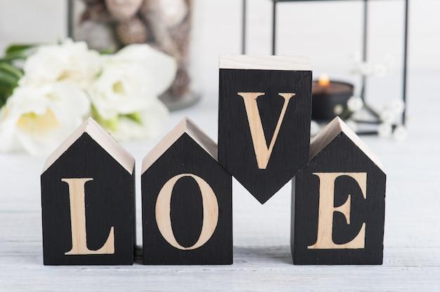 Fleurs et bougie allumée, lettre en bois love