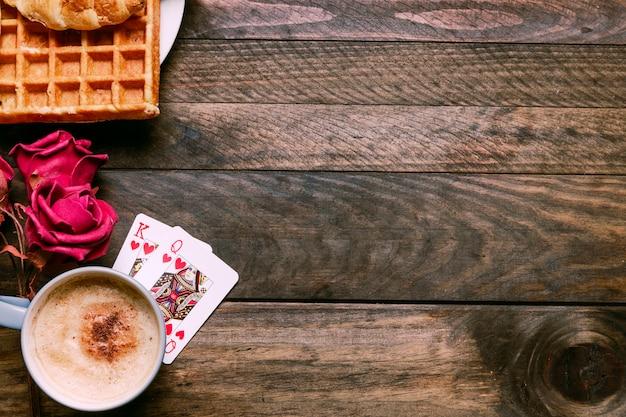 Fleurs, boulangerie sur assiette, cartes à jouer et tasse de boisson