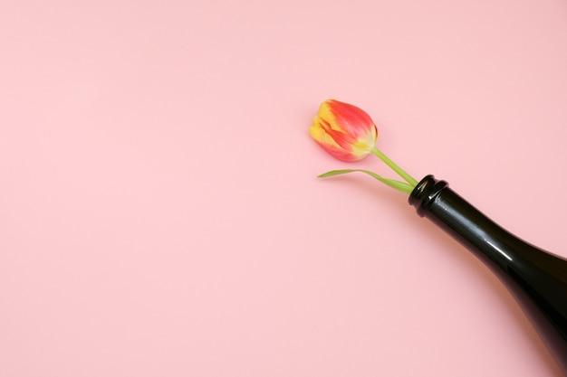 Fleurs en bouteille sur fond rose tendresse. le concept de l'anniversaire