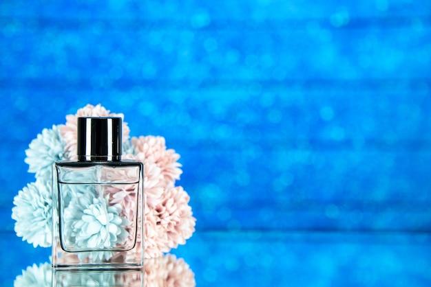 Fleurs de bouteille de parfum vue de face sur fond bleu avec espace libre