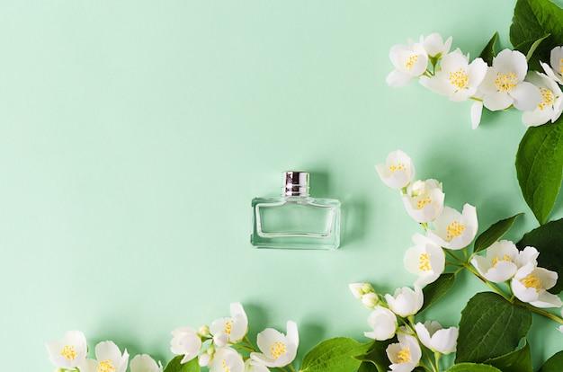 Fleurs et branches de jasmin et parfum sur vert. pose à plat