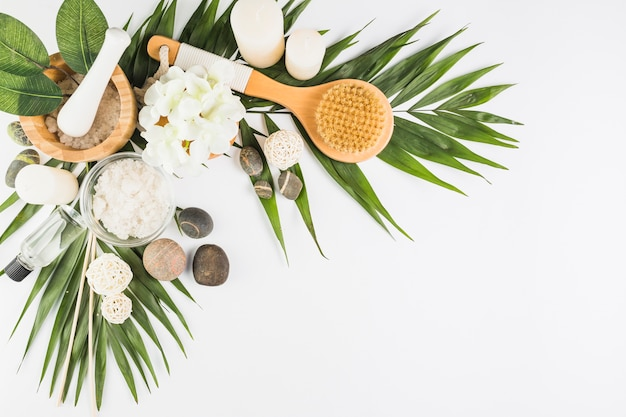 Fleurs; brosse; pierres de spa; sel; bougies; bouteille d'huile sur une surface blanche
