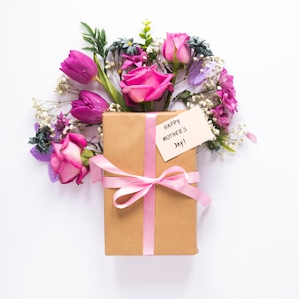 Fleurs avec cadeau et inscription fête des mères heureux