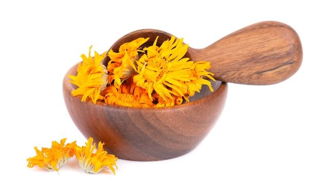 Fleurs de calendula séchées dans un bol en bois et une cuillère, isolées sur fond blanc. pétales de calendula officinalis. herbes medicinales.