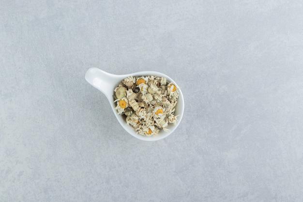 Fleurs de camomille séchées dans un bol blanc.
