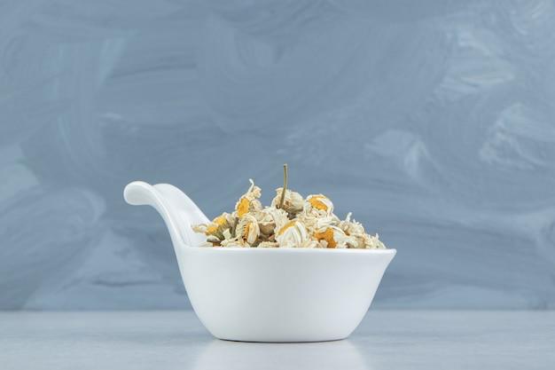 Fleurs de camomille séchées dans un bol blanc