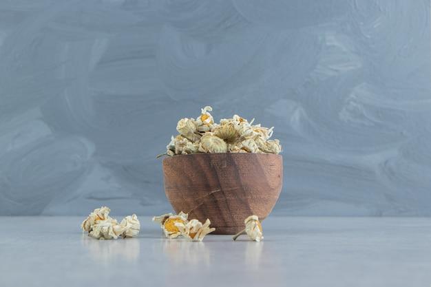 Fleurs de camomille séchées dans un bol en bois.