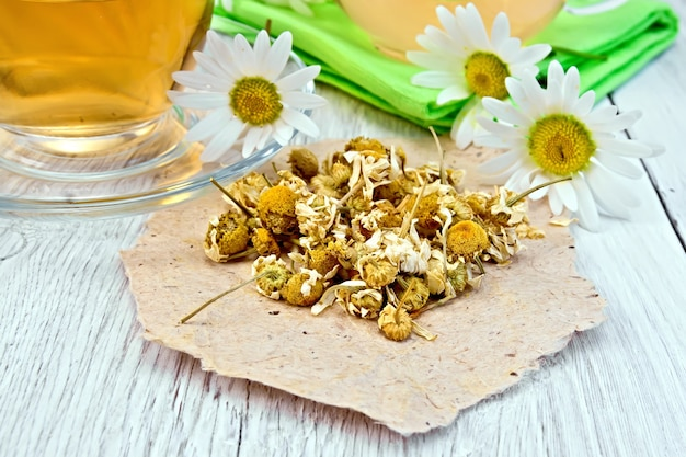 Fleurs de camomille séchées sur papier, thé dans une théière en verre sur une serviette et une tasse, fleurs de camomille fraîches sur fond de planches de bois