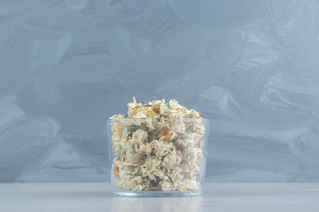 Fleurs de camomille sèches dans un bol en verre.