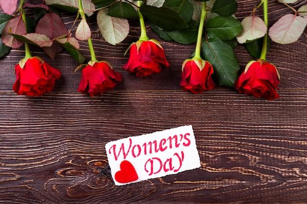 Fleurs avec carte de la journée de la femme. roses rouges et fond en bois. chérissez votre chéri. cadeau romantique en vacances.