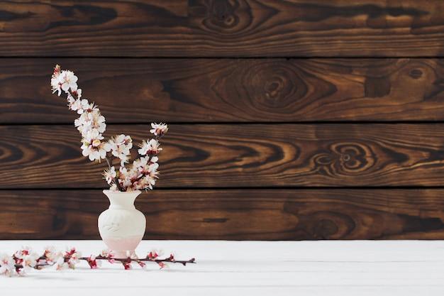 Fleurs de cerisier dans un vase sur une surface en bois