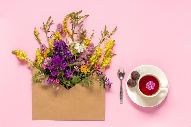 Fleurs de champ dans une enveloppe d'artisanat et une tasse de thé aux herbes