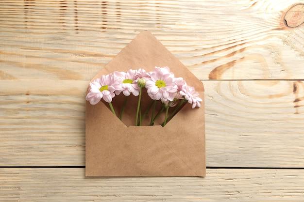 Fleurs de chrysanthème d'automne dans une enveloppe sur une table en bois naturel. vue de dessus