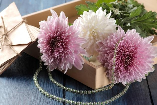 Fleurs de chrysanthème d'automne avec des perles et des lettres sur une table bleu foncé