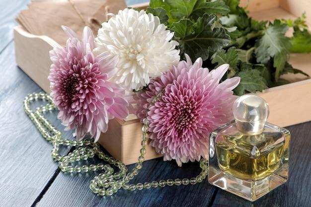 Fleurs de chrysanthème d'automne avec des perles et des spiritueux sur une table bleu foncé