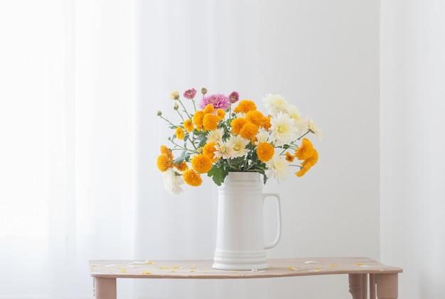 Fleurs de chrysanthème dans une cruche blanche à l'intérieur blanc