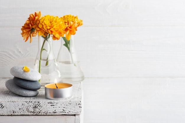 Fleurs de chrysanthème orange avec cailloux et bougie d'arôme sur table rustique blanche
