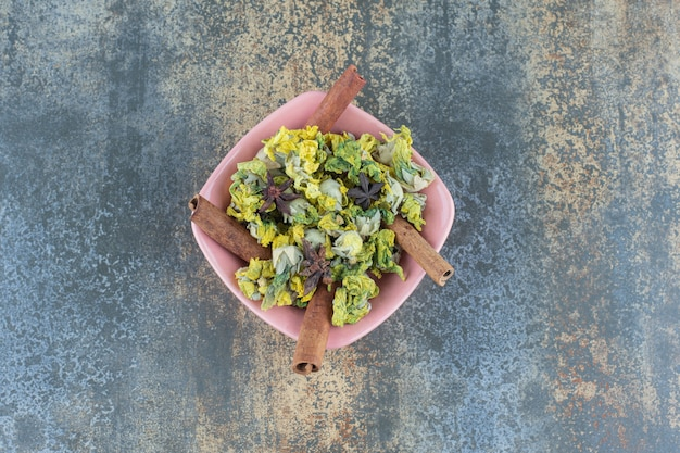 Fleurs de chrysanthème séchées et cannelle dans un bol rose.