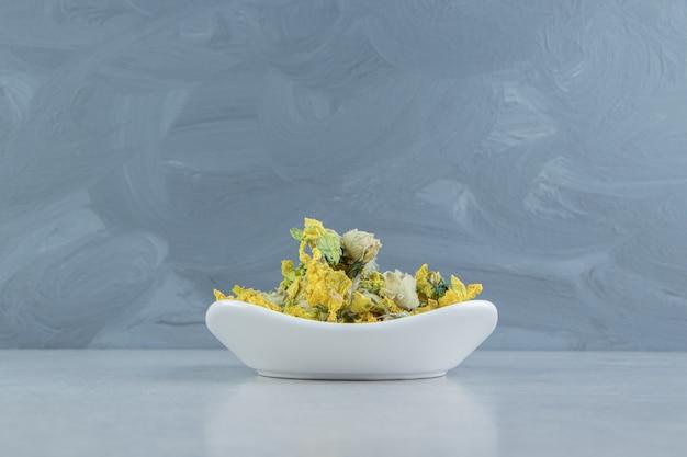 Fleurs de chrysanthème sèches dans un bol blanc.