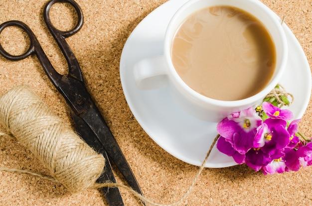 Fleurs, ciseaux et jute à côté d'une tasse de café.