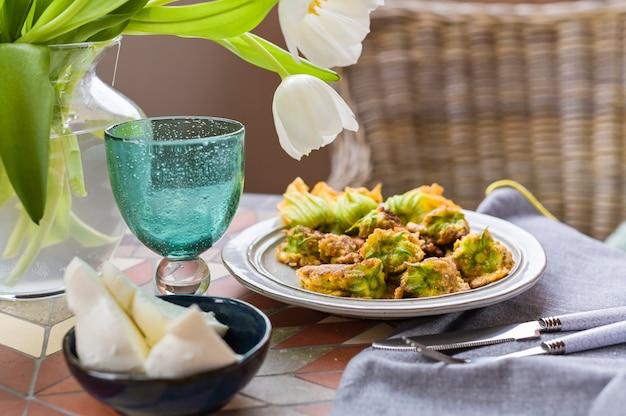 Fleurs de citrouille frites dans la pâte. plat italien traditionnel. dîner et fleurs à la maison