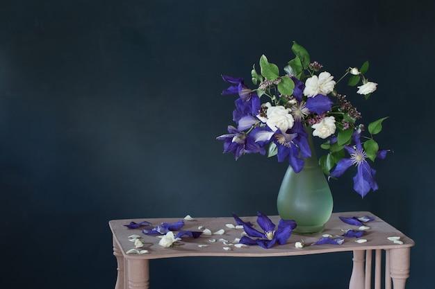Fleurs de clématites dans un vase en verre sur une étagère en bois vintage
