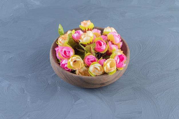 Fleurs colorées dans un bol, sur fond blanc.