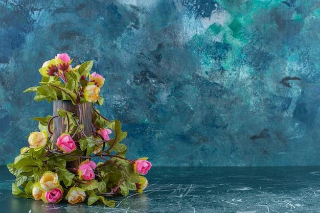 Fleurs colorées dans une cruche en bois, sur fond bleu.