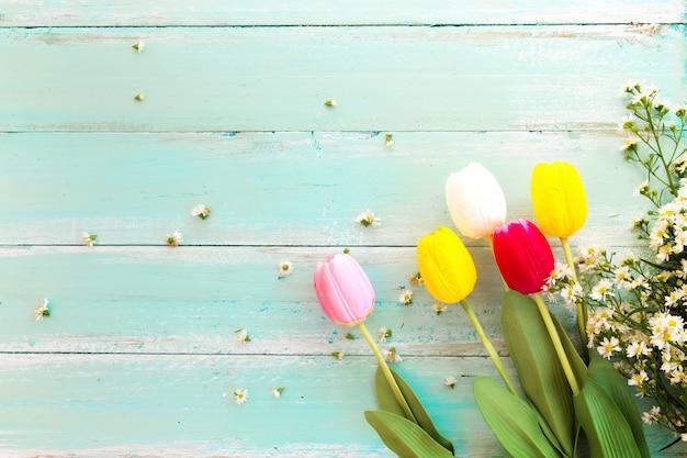 Fleurs colorées sur fond en bois vintage, vue de dessus
