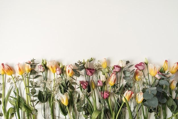 Fleurs colorées: tulipes, eucalyptus, roses sur blanc