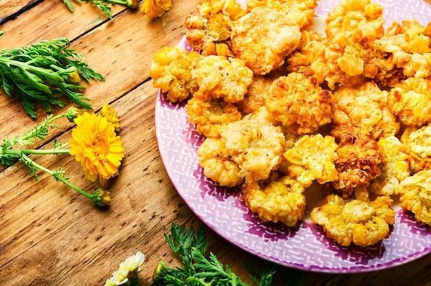 Fleurs comestibles frites savoureuses. fleurs de chrysanthème en pâte. fleurs frites