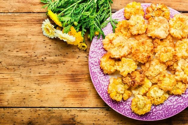 Fleurs comestibles frites savoureuses. fleurs de chrysanthème en pâte à frire.fleurs frites.copy space