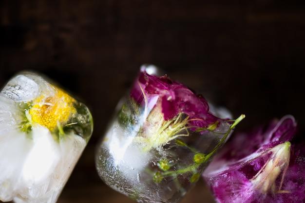Fleurs congelées dans des cubes de glace sur fond en bois rustique