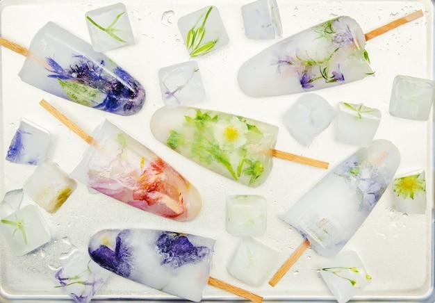 Fleurs congelées dans des glaçons et de la crème glacée sur un bâton. mise au point sélective.