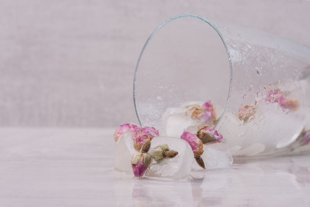Fleurs congelées dans des glaçons sur une surface blanche.