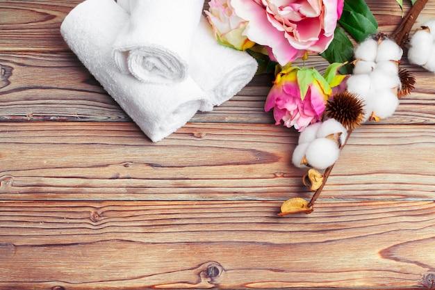 Fleurs de coton avec une serviette sur une table en bois