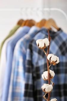Fleurs de coton et vêtements suspendus sur une grille dans un dressing