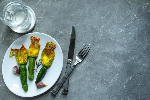 Fleurs de courgettes frites farcies de fromage à la crème à l'ail sur plaque blanche. copier l'espace