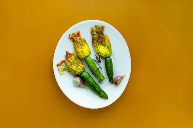 Fleurs de courgettes frites farcies de fromage à la crème à l'ail sur une plaque blanche sur le fond de couleur moutarde au miel