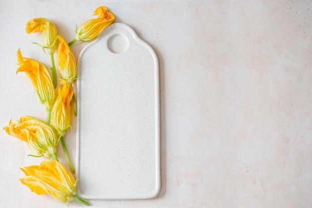Fleurs de courgettes sur un tableau blanc