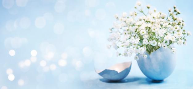 Fleurs dans un oeuf de pâques bleu avec des lumières bokeh