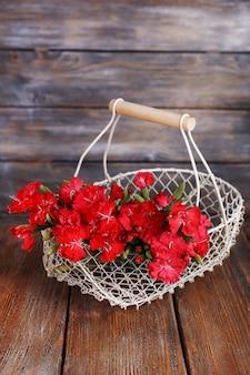 Fleurs dans le panier sur fond de bois