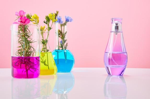 Fleurs dans des tubes à essai et une bouteille de produit cosmétique. concept de recherche de parfum et de parfum.