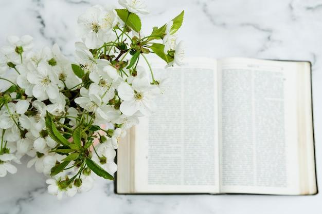 Fleurs dans un vase et une bible ouverte à plat sur la table