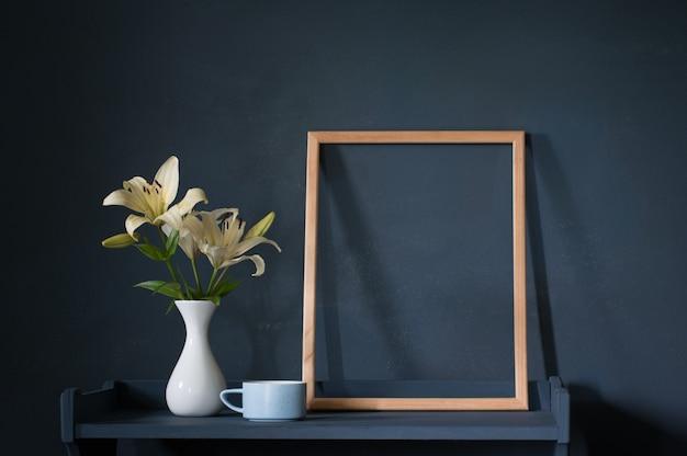 Fleurs dans un vase et cadre en bois sur mur sombre de fond