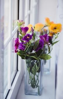 Fleurs dans un vase sur la fenêtre