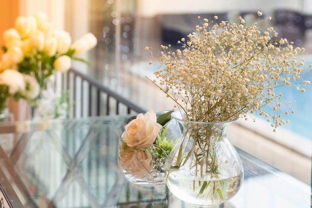 Fleurs dans un vase placé à côté du verre près de la piscine